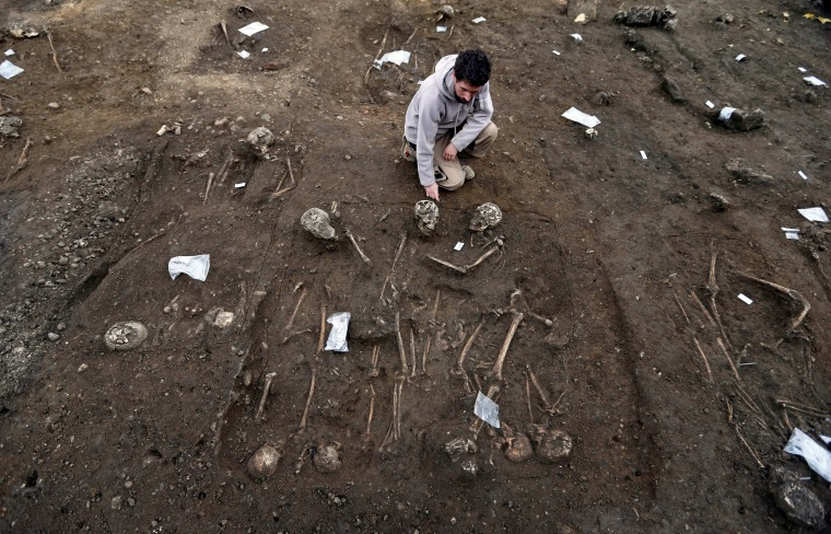 Image: An archeologist looks at partial skeleton remains, with skull and bones, from an ancient burial area that was excavated at a building site in Bordeaux
