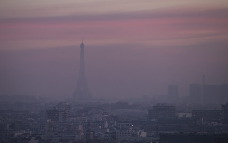 Image: The Eiffel tower is shrouded in haze as the sun comes up