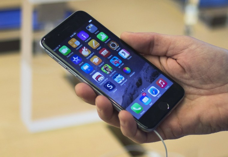 Image: A customer holds an iPhone 6 on display at the Fifth Avenue Apple store on the first day of sales in Manhattan.
