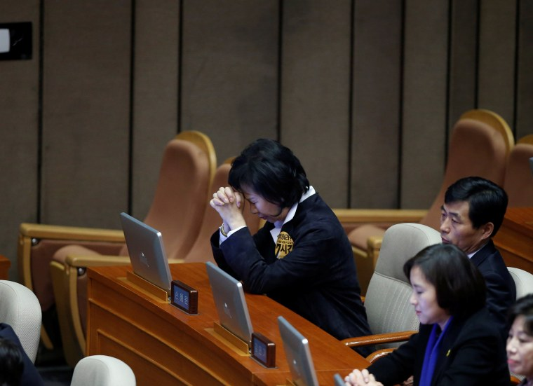 Image: A lawmaker prays after voting on the impeachment bill of South Korean President Park Geun-hye at the National Assembly in Seoul