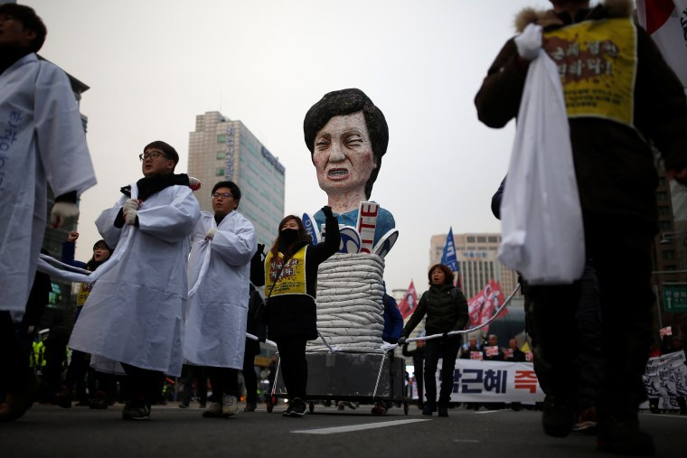 Image: Members of Korean Confederation of Trade Unions march with an effigy of South Korean President Park Geun-hye during a general strike calling for Park to step down in central Seoul