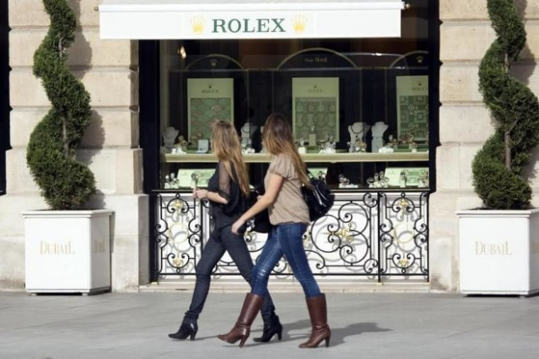 Women walk past a window display of luxury goods maker Rolex in Paris' Place Vendome