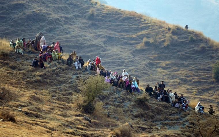 Image: Pakistani villagers gather near a plane crash site in the village of Saddha Batolni
