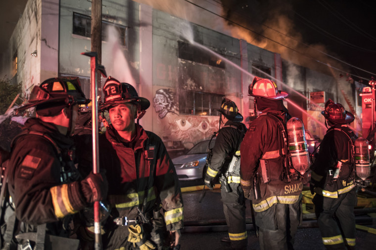 Image: Firefighters battle a fire at a converted Oakland warehouse