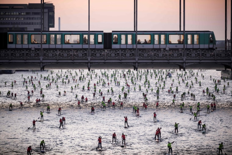 Image: People take part in the Nautic SUP Paris Crossing stand up paddle competition on the Seine river