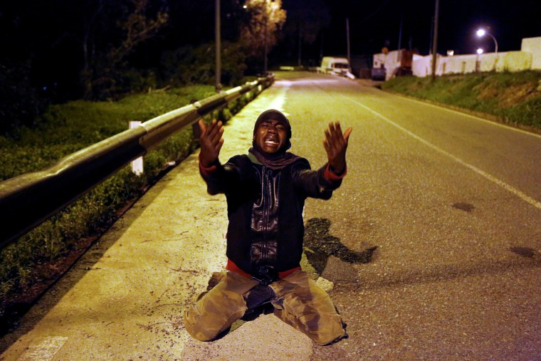 Image: An African migrant reacts on a road after crossing the border fence between Morocco and Spain's north African enclave of Ceuta
