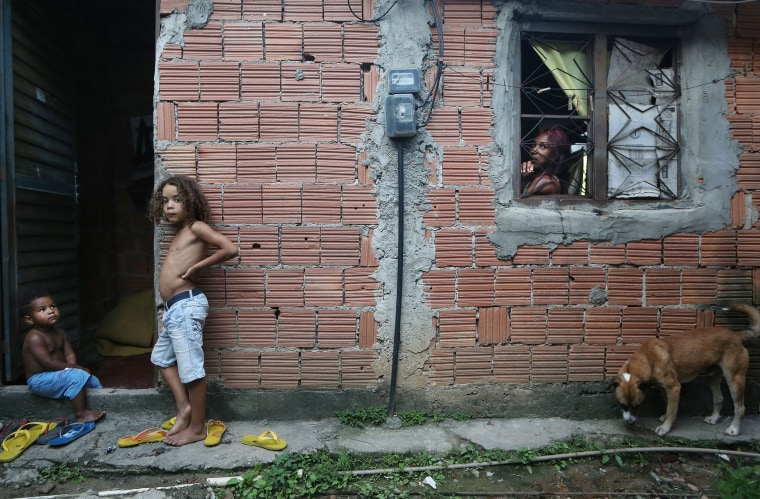 Image: Residents gather at the front of a small house that holds fifteen people in the Mangueira 'favela' community