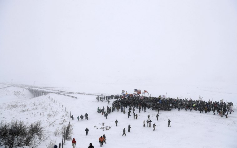 Image: Military veterans march to a closed bridge outside the Oceti Sakowin camp