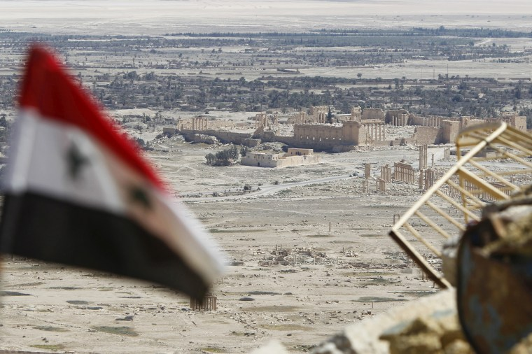 A Syrian national flag flutters as the ruins of the historic city of Palmyra are seen in the background, in Homs Governorate.