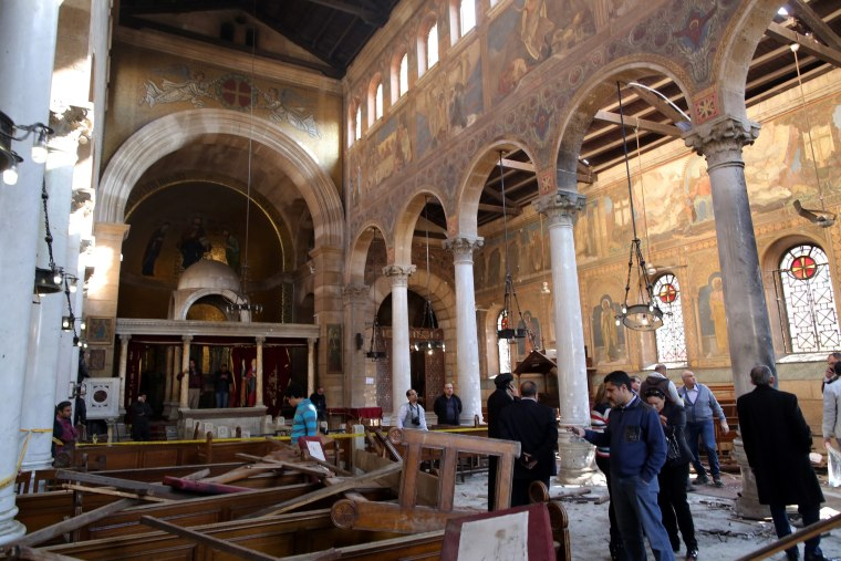 Image: Security officials and people inspect the damage inside St. Peter and St. Paul Coptic Orthodox Church