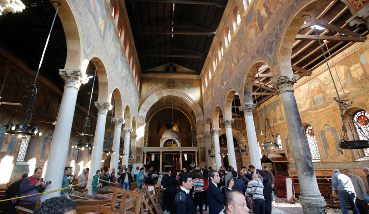 Image: Egyptian security officials and investigators inspect the scene following a bombing inside Cairo's Coptic cathedral in Egypt