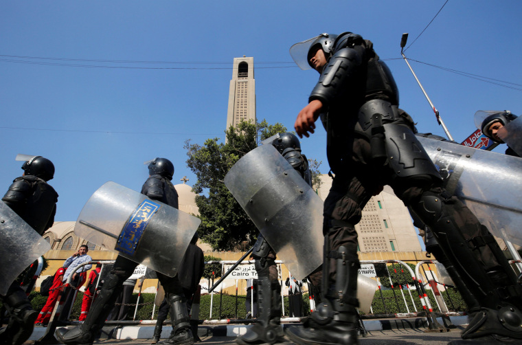 Image: Members of the special police forces stand guard to secure the area around Cairo's Coptic cathedral after an explosion inside the cathedral, Egypt