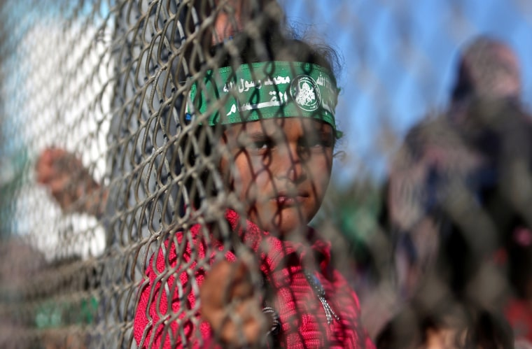 Image: Palestinian girl stands behind a fence during a rally marking the 29th anniversary of the founding of the Hamas movement, in Khan Younis in the southern Gaza Strip