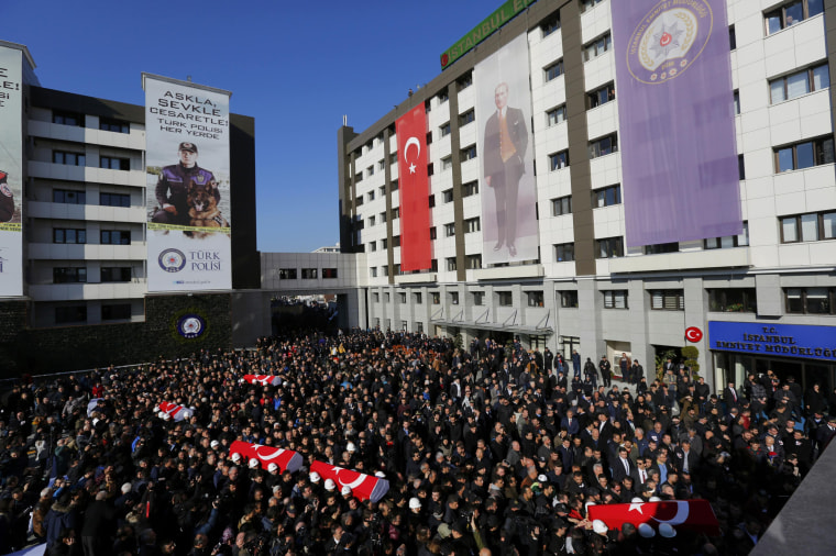 Image: People carry the flag-draped coffins of police officers killed in Saturday's blasts in Istanbul