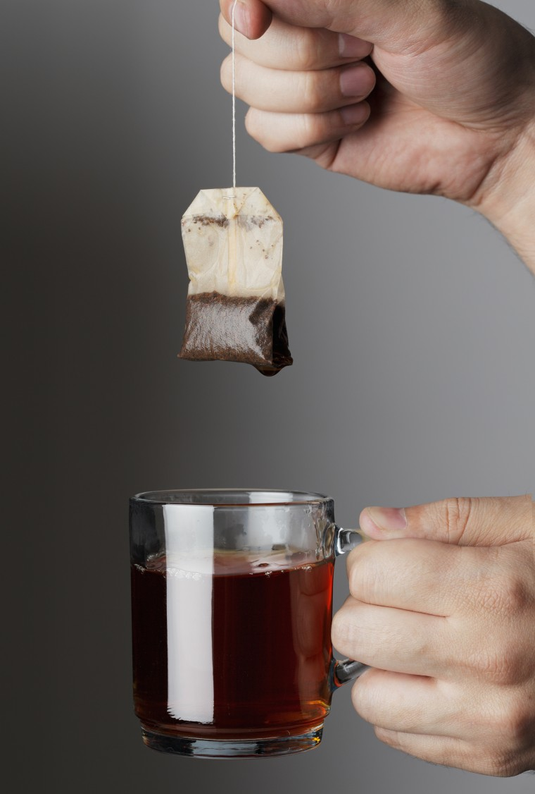 Hand lifting a used tea bag from a glass tea mug.