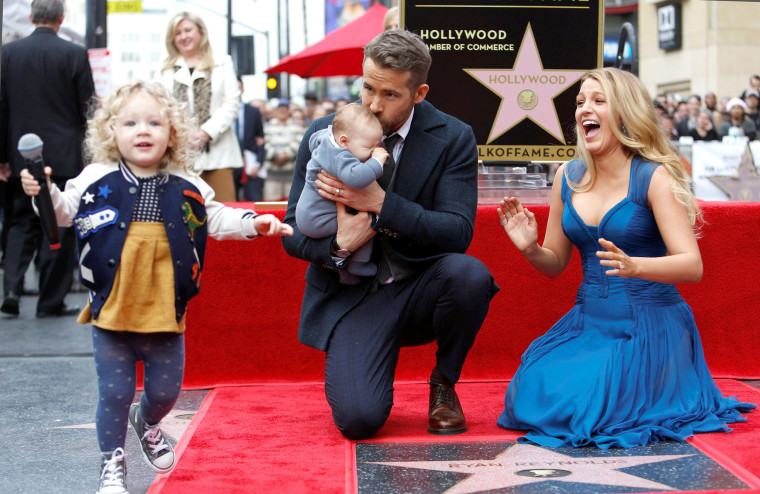Reynolds kisses his daughter while posing by his star with his wife Lively and their daughter James on the Hollywood Walk of Fame in Hollywood