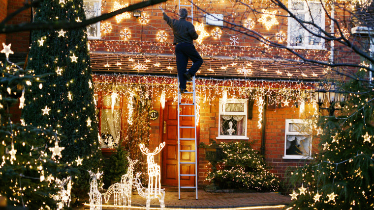 Man hanging Christmas lights outside.