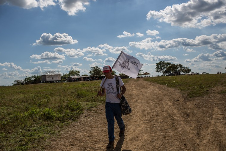 An attendee to the vigil arrives to the camp carrying a white flag many of the people gathered were from the region and also from the capital Bogot?.