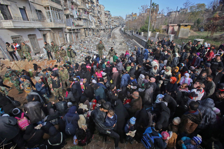 Image: Syrian residents fleeing violence in Aleppo gather at a checkpoint