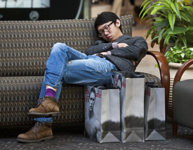 A man sleeps on a couch after shopping at Abercrombie & Fitch at South Park mall in Charlotte