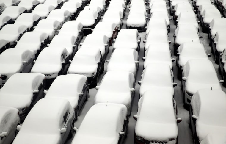 Image: Snow covers vehicles in a rental car parking lot at O'Hare International Airport