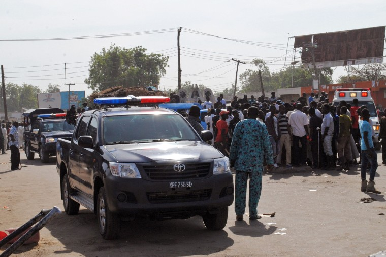 Image: Emergency services and soldiers gather at the scene of a suicide bomb attack in a market in Maiduguri