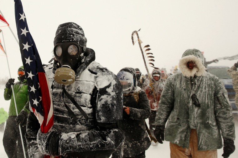 """Image: A man takes part in a march with veterans to Backwater Bridge just outside of the Oceti Sakowin camp during a snow fall as \""""water protectors\"""" continue to demonstrate against plans to pass the Dakota Access pipeline"""