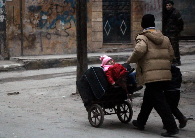 Image: Civilians flee the Sukkari neighborhood towards safer areas in southeastern Aleppo, Monday.