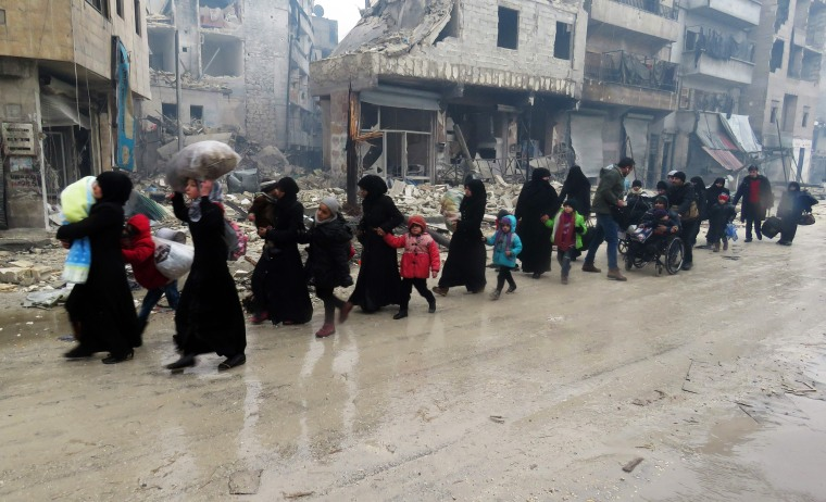 Image: Syrian residents, fleeing violence in the restive Bustan al-Qasr neighborhood, arrive in Aleppo's Fardos neighborhood on Dec. 13 after regime troops retook the area from rebel fighters.