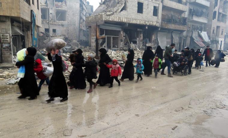 Image: Syrian residents, fleeing violence in the restive Bustan al-Qasr neighborhood, arrive in Aleppo's Fardos neighborhood on Dec. 13 after regime troops retook the area from rebel fighters.