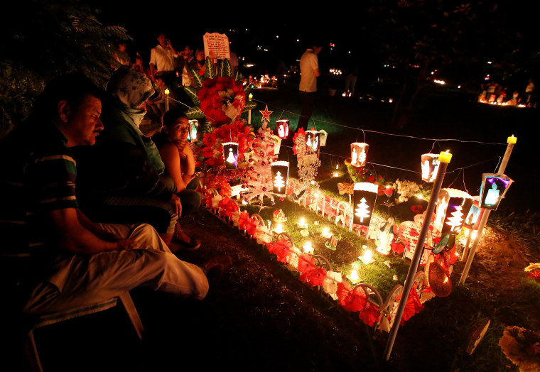 """Image: People light candles, next to a grave in the cemetery \""""Jardines de la Aurora\"""", to mark the beginning of the Christmas festivities, in Cali"""