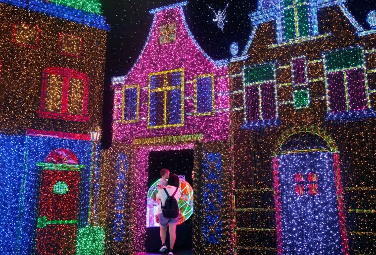 Image: People tour a Christmas attraction featuring a display of more than 800,000 light bulbs in Universal Studios Singapore