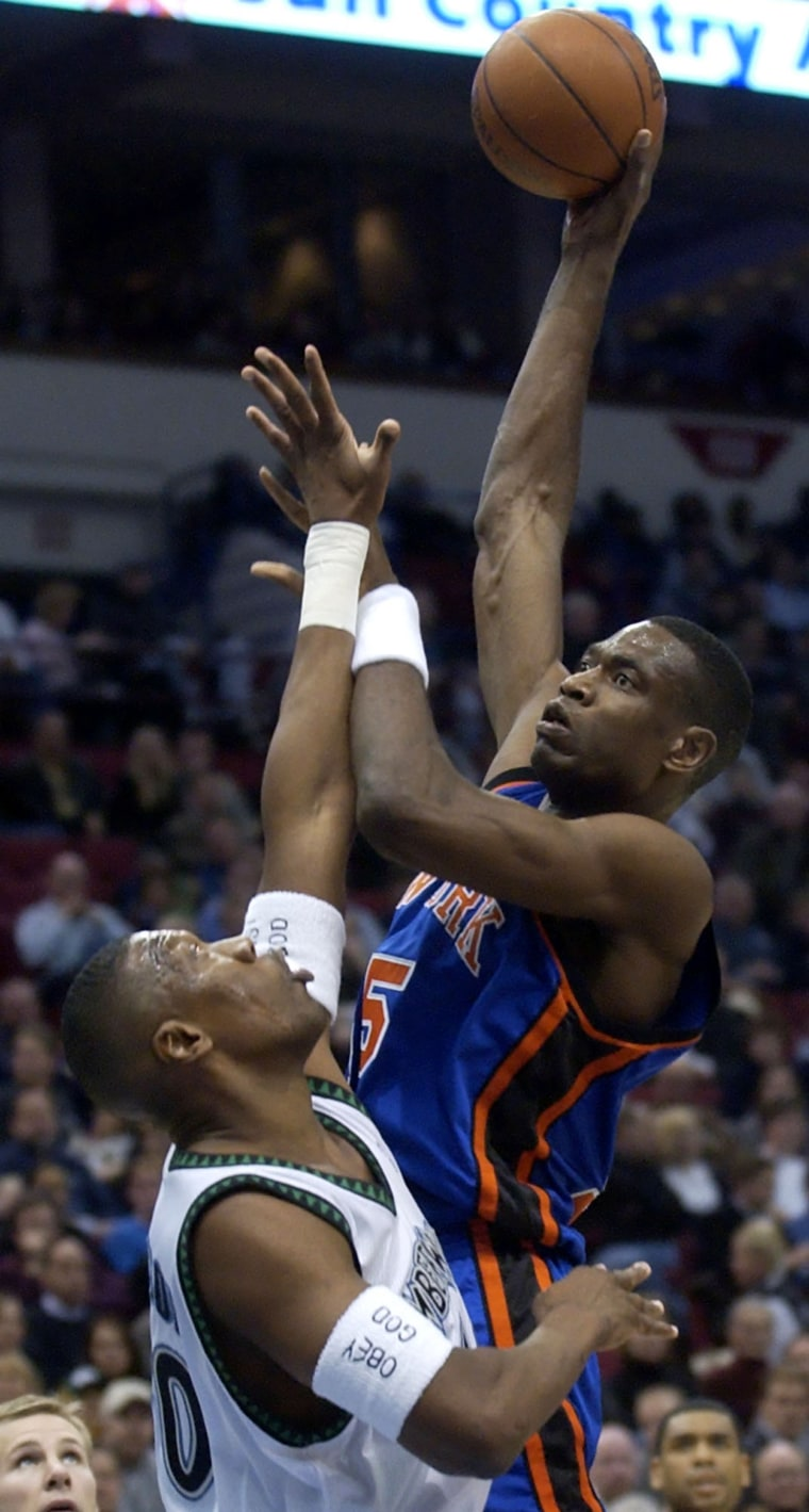 Image: Minnesota Timberwolves center Ervin Johnson, left, can't stop a shot by New York Knicks center Dikembe Mutombo