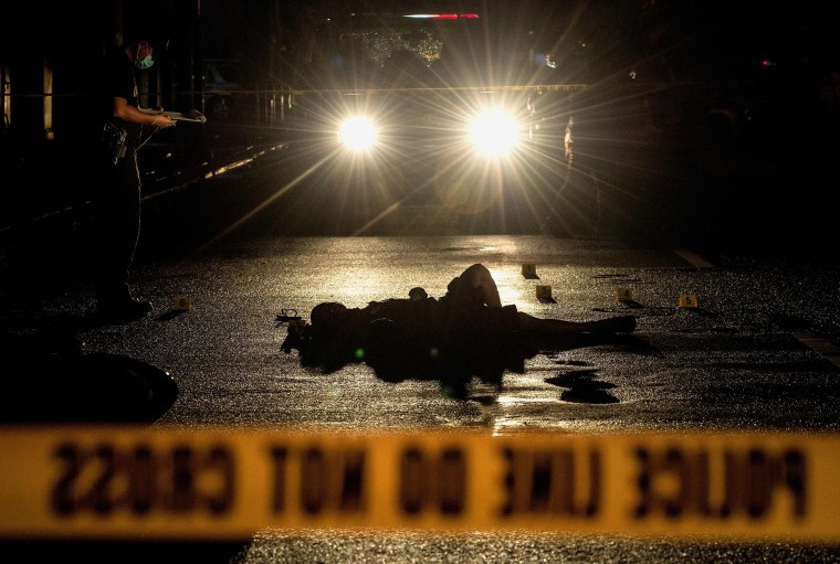 Image: This picture taken on October 29, 2016 shows police officers investigating a crime scene where two alleged drug dealers were gunned down by unidentified men in Manila.