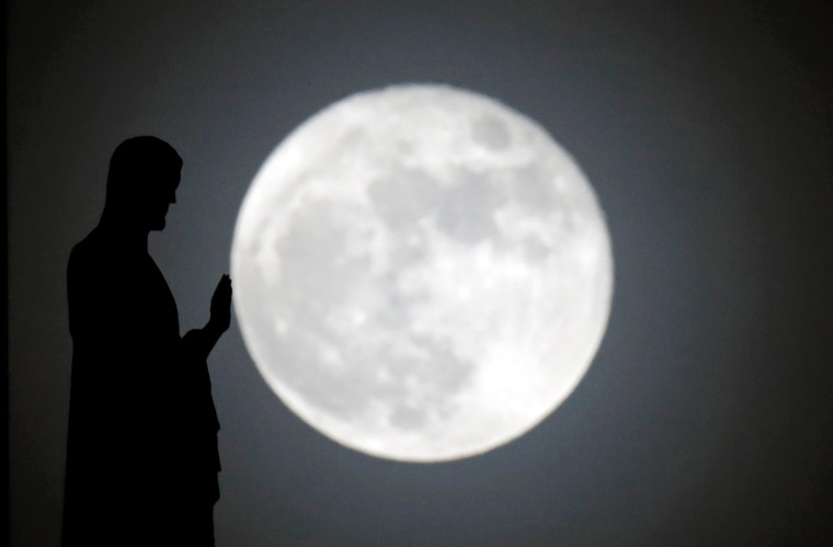 Image: A statue on the roof of Notre-Dame cathedral is silhouetted in front of a supermoon in Paris