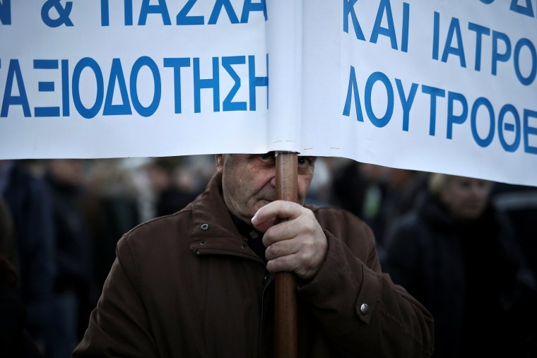 Image: A Greek pensioner holds a banner during a demonstration against government policies affecting pensioners in Athens