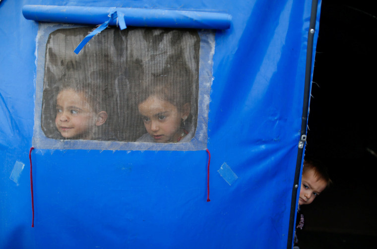 Image: Displaced Iraqi children, who fled the Islamic State stronghold of Mosul, look through a window in a tent in Khazer refugee camp