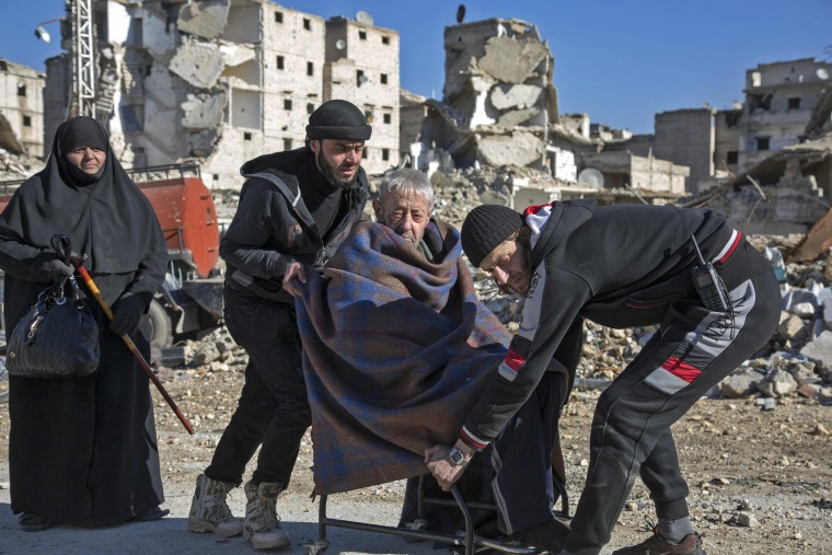 Image: An elderly Syrian man is carried during an evacuation operation of rebel fighters and their families  from rebel-held neighborhoods on Dec. 15, in the embattled city of Aleppo.