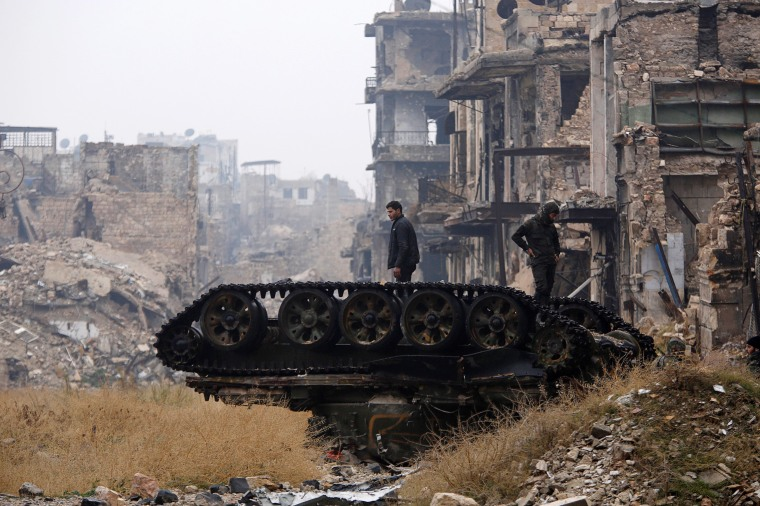Image: Forces loyal to Syria's President Bashar al-Assad stand atop a damaged tank near Umayyad mosque, in the government-controlled area of Aleppo, during a media tour, Syria, Dec. 13.