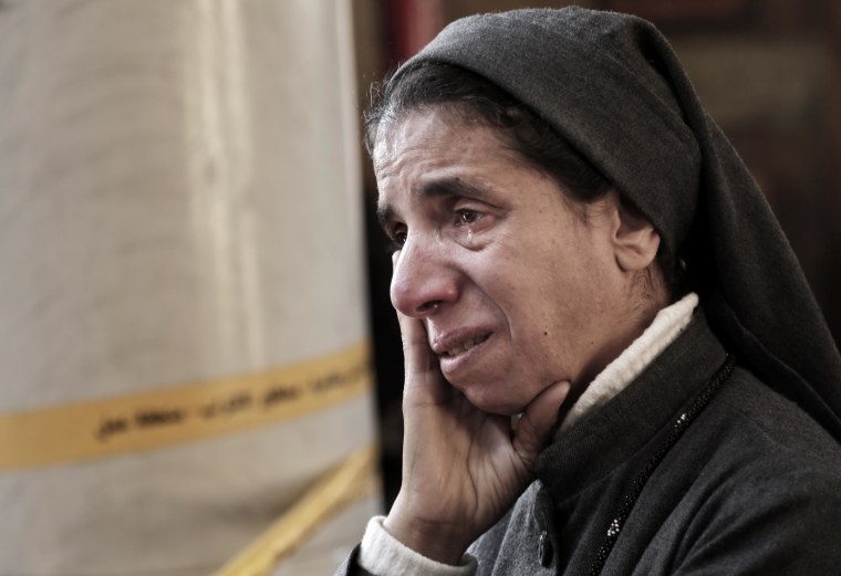 Image: An Egyptian Coptic nun weeps as she looks at damages inside the St. Mark Cathedral in central Cairo, following a bombing, Dec. 11.
