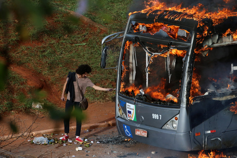 Image:A man lights up his cigarette with the flames of a bus burned by anti-government demonstrators during a protest against the constitutional amendment PEC 55, which limits public spending, in front of Brazil's National Congress in Brasilia.