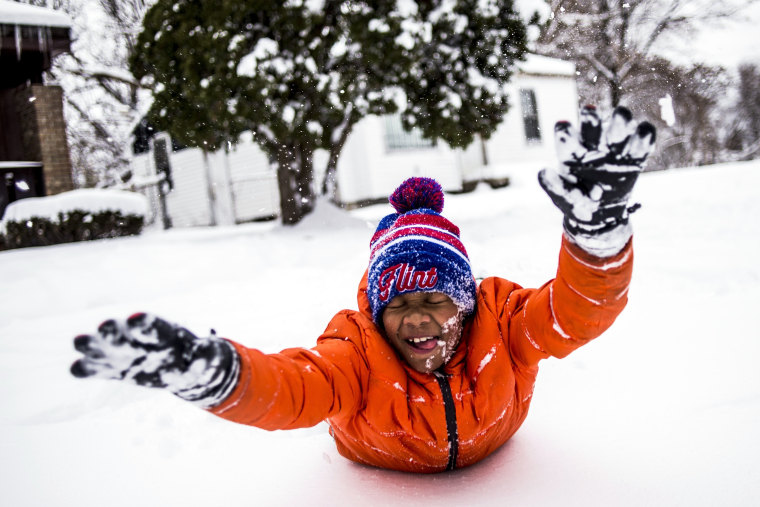 Image: Steven Washington, 9, dives faces first into a fresh pile of snow, taking a break from shoveling his grandmother's driveway after school was called off for a snow day Monday, Dec. 12, on Flint, Michigan's north side.
