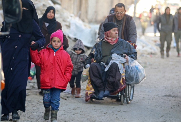 Image: People walk as they gather to be evacuated from a rebel-held sector of eastern Aleppo