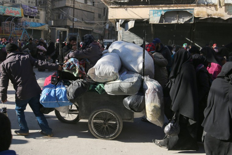 Image: People walk with belongings as they gather to be evacuated from a rebel-held sector of eastern Aleppo