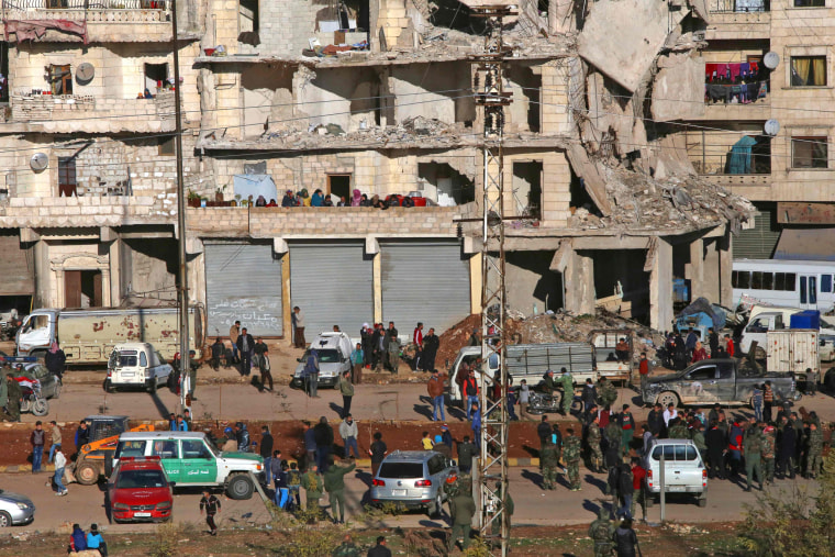 Image: Residents in a government-held part of Aleppo's Salaheddin neighborhood watch from their damaged homes as buses evacuate rebel fighters and their families