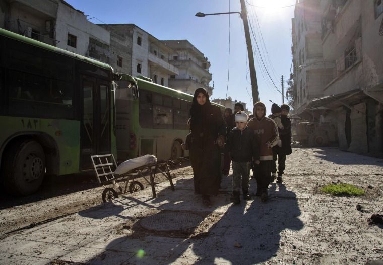 Image: Syrians gather during an evacuation operation of rebel fighters and their families from rebel-held neighborhoods