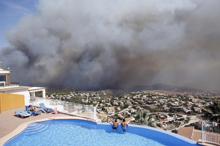 Image: Two men look at a wildfire from a swimming pool as it burns nearby Benitachel village, eastern Spain
