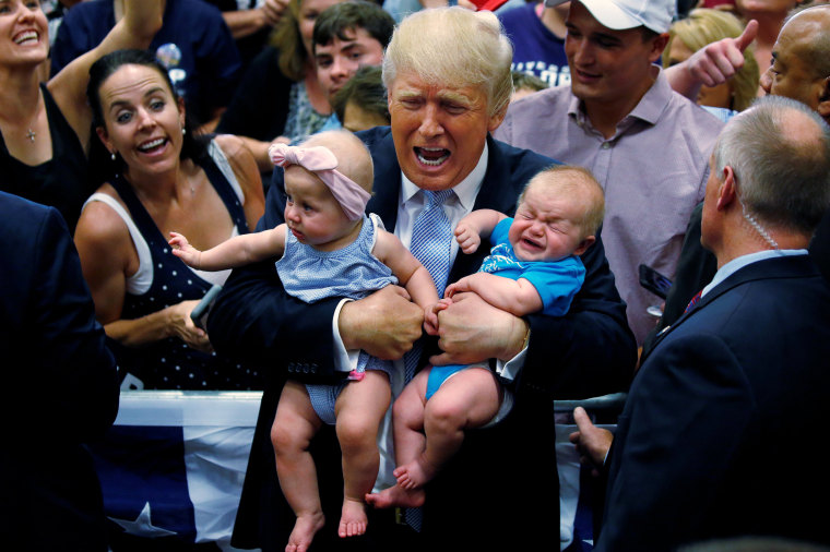 Image: Republican presidential nominee Donald Trump holds babies at a campaign rally in Colorado Springs,