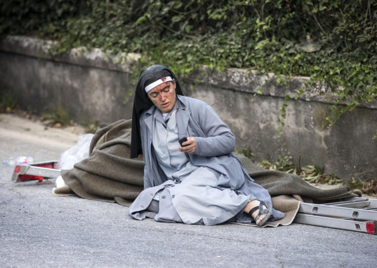 Image: Sister Mariana, from Albania, checks her mobile phone as she lies near a victim laid on a ladder following an earthquake in Amatrice Italy
