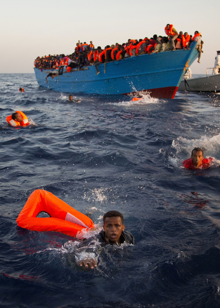 Image: Migrants, most of them from Eritrea, jump into the water from a crowded wooden boat
